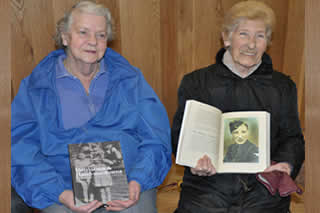 Harriet Donnelly (right) shows Margaret Taylor (left) a photo of her brother John Donnelly ( published in the book).