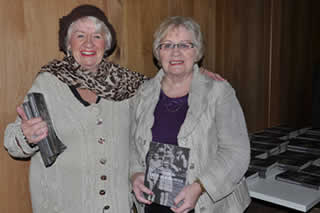 Marie Redmond & Irene Redmond who appeared as children on the cover of the book stand by a stack of the books.